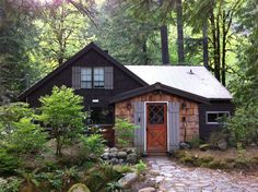an enchanted cottage in the forest. i like the ideal of shutters either side of the front door.