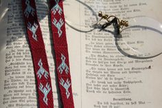 Tablet woven braid decorated as a bookmarker on a book of poems by Heinrich Heine. Silk Nm 22, 1,1 cm Design of a Seal Tag dated about 1200 from Scotland Tablet woven by Sylvia Crumbach