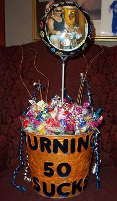 My husband doesn't Pin - so here's the 50th Sucks Lollipop Bucket I made for his party. That's a picture of him on the center balloon too :)