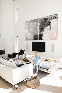 rustic elements and pure contemporary white for a modern living room - great way to incorporate the t.v. as part of the artworks