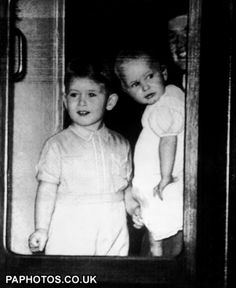 Prince Charles and Princess Anne, apparently in the window or doorway of a train and seemingly rather happy about it.