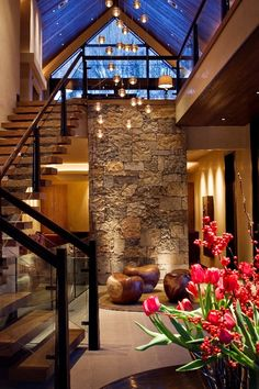 beautiful entry of a home in Aspen, Colorado, designed by Knudson Interiors. Love the stone, stairs, lighting and window. Not a fan of the bean shaped chairs.