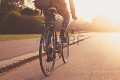 A young woman cycling into the sunset in the park Stock Photo