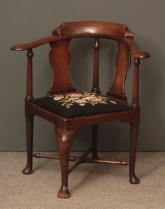 A mid 18th Century mahogany corner armchair with horseshoe patterned back and twin solid shaped splats, the drop in seat upholstered in tapestry