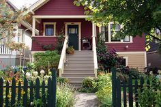 I like cottage gardens and informal, open fences, but was having trouble imaging a white picket fence (any fence, really) with my Craftsman home. Seems like painting the fence darker might be all it takes.