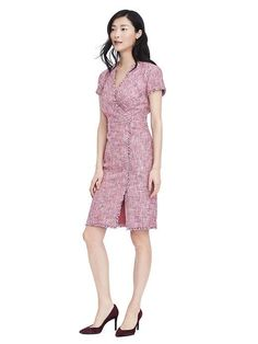 Feminine pink tweed meets an on-trend silhouette in our fringe-trim frock. V-neck. Short sleeves. Invisible back zip. Drape-front styling. Fully lined.