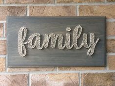String Art - family on a grey stained wood board.