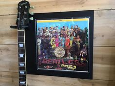 Original (used, fair condition) The Beatles - Sargent Peppers Lonely Hearts Club Band LP / Album Jacket, Guitar / Bass Holder. (VINYL RECORD AND GUITAR NOT INCLUDED)  The 'sacredness' of a record is connected to its uniqueness. Vinyl, for many was and is a way to complete an artist's discography and ends up being even more meaningful as an outward sign or artifact of fandom. Vinyl is also the representation in the form of putting our records in a prominent place like a living room w...