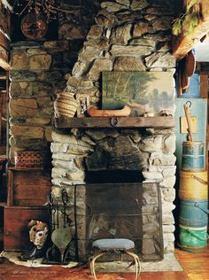 old-timey cabin look of a fireplace - love the canoe and art and stool