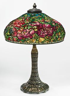 """Tiffany Studios -  AN IMPORTANT """"ELABORATE PEONY"""" TABLE LAMP -    with a rare """"Arch and Leaf"""" base  shade impressed TIFFANY STUDIOS NEW YORK 1903 base impressed TIFFANY STUDIOS/NEW YORK/542 leaded glass and patinated bronze, 32 1/2  in. (82.6 cm) high 23 in. (58.4 cm) diameter of shade circa 1910"""