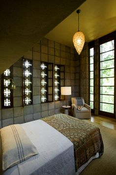 The petite master bedroom. The concrete blocks create a sense of protection and seclusion, while the high ceiling prevents the room's modest footprint from triggering claustrophobia.