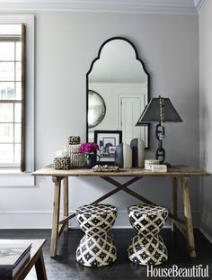 The corner of the master bedroom features a vanity with a mirror from Mecox, a console table by B.D. Jeffries and stools from Palecek. Click through for more design inspiration from Jill Sharp Weeks' Charleston rental home.
