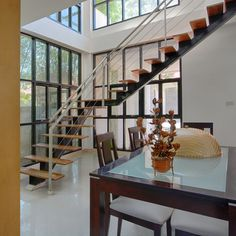 Two story kitchen and dining area with modern steel and wood staircase