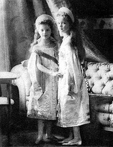Russian Grand Duchesses Tatiana, left, and Olga Nikolaevna dressed in court dress, ca. 1904 standing before a Chesterfield sofa.