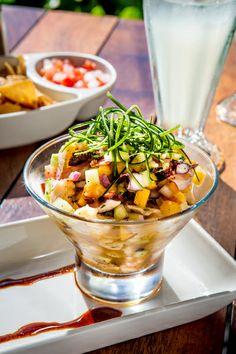 Mango-Caribe Ceviche  Shrimp, octopus, grouper, mango, red onion, mint, cucumber, cilantro, passion fruit juice, coconut cream & chile cascabel