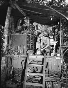 US Army Private First Class George Chapman and Sergeant John Eppard working at the Mobile Machine Shop truck of 741st Ordnance Company, 41th Infantry Division at Horanda, New Guinea, 9 May 1943....