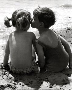 Fotografia de pessoas, foto do momento de um beijo amigo entre duas crianças.