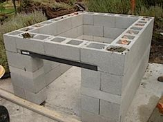 DIY easy concrete block BBQ pit {VIDEO}. Less than 250$. The one shown in this photo has an added steel bar for a more permanent installation. You could also add concrete in the blocks for structural support and face the block with brick for aesthetics. The one in the video is intended for easy transport or take-down.