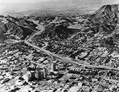 (ca. 1960s)*^ - Aerial view of Hollywood and its surrounding areas. Cars may be seen travelling the Hollywood Freeway. Traffic going north is towards the Valley, going south is towards Los Angeles. The Hollywood Reservoir can be seen is in the hills above Hollywood.