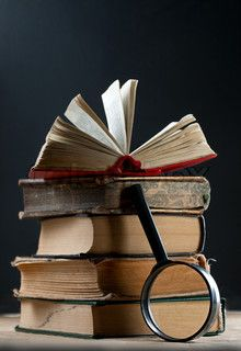 Image of 'Pile of old books with magnifying glass'