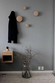 Peindre un couloir. Un mur gris et un manteau noir qui est suspendu.
