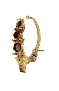 Gold earring with colored stones. It ends in a lynx's head with emerald eyes, and an emerald between the ears. From the mouth of the cat hang three colored stones, set in gold; the cat's neck ends in three beads of colored stone, separated by filigree. Some of the stones, and the hook of the earring, are missing. This earring forms a pair with 98.772.