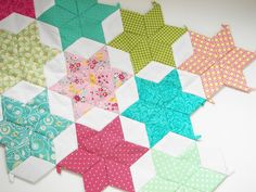 like the six-pointed star quilt idea, though I would do away with the basting step & just cut precisely using a template, then piece together.