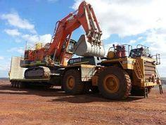 Komatsu 2500 mine de pelle étant mû par un camion de transport Cat 785 avec une très grande remorque.