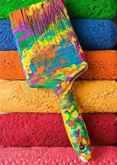 Paintbrush covered with dried paint atop used paint rollers by Garry Gay on Getty Images