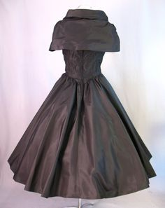 ■Dress is fashioned from crisp black taffeta that probably has some silk content.  ■Fitted bodice is fully boned and fits tightly to the body with many vertical seams and darts.  ■Bodice comes to a shallow V at the front.  ■3 self-fabric roses are attached at the front neckline.     ■Shoulder drape collar is attached at the front armhole and has tucks to give it shape where it fits at the top of the arms