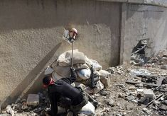 A Free Syrian Army fighter holds the head of a mannequin up to a hole in a wall of a Syrian Army base to attract and locate a sniper during heavy fighting in the Arabeen neighbourhood of Damascus