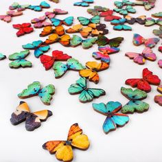 Wooden Butterfly Buttons, mixed designs, 50 pack – These colourful wooden butterflies are sweet and eye-catching. They are flat (perfect for gluing) with 2 holes (perfect for stringing), coloured side is lacquered,  with natural wood on the reverse. Adorn your wedding invites, favours, table decor or after-event Thank You cards. Come in a pack of 50.  -Size: 28 x 21 x 3mm approx. -Quantity: 50pcs/lot -Material: Wood -Colour: Multi-coloured mixed