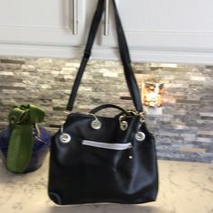 "Black PU Leather Purse. an eye catcher  Adjustable strap. Outer and inner pockets jazzed up with silver zipper accents.  Large Silver Hoop Grommets surround.  Floral lining. Measures  13"" wide by 11"" deep. Rise adjusts. Bags Hobos"