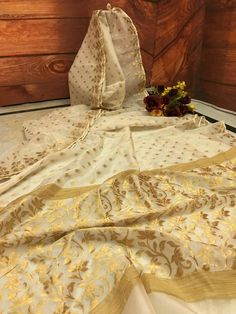 An elegant yet Royal combination of Off-White with Golden Zari combination makes this Resham Handloom Saree an unique piece by its own. If you are looking to stand out in the crowd, this is a must have ! White And Gold Saree, Gold Silk Saree, White Saree, Indian Bridal Sarees, Indian Silk Sarees, Soft Silk Sarees, Dhakai Jamdani Saree, Handloom Saree, Kurti