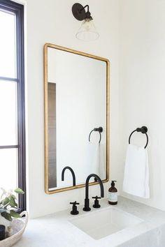 salle de bain en noir et blanc. Miroir doré