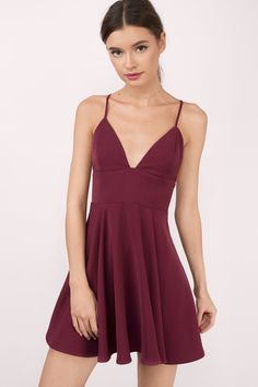 A classic skater dress with deep v neckline and spaghetti straps. Straps cross in the back and tie together in a knot in the center of the back. Zipper on the side with a hook and eye closure. Available in wine, cobalt, and black.