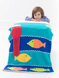 Whimsical children's blanket/throw that incorporates stripes and intarsia. Fish and Octopus charts are worked in intarsia, following chart. Wave chart is worked in stranded colorwork.
