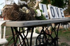 Renovated Singer sewing table with wrough iron base. Ideal as a table for signing wedding certificates. Styled with antique books, birds nest, quails eggs, 'LOVE' painted signage, flowers in milk jug, and embroidered linen table runner.