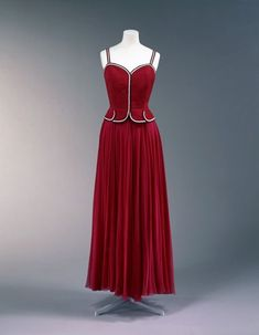 Coco Chanel (1883-1971) did things her own way, including upgrading sportswear to evening wear in this 1938 summer evening gown.  The navy, white, and red grosgrain trim pays homage to her love of boating.