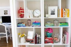 styling a bookshelf (1. color coordinating books makes it visually more appealing 2. fresh flowers and framed cards as cute accents 3. can be used to store extra kitchen items, such as stemware 4. fill pretty glass jars with colorful candy)