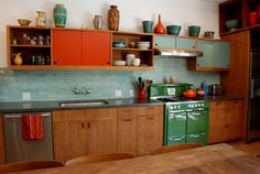 Green stove, teal back splash & cabinets with a splash of awesome orange. Holy in love, Batman