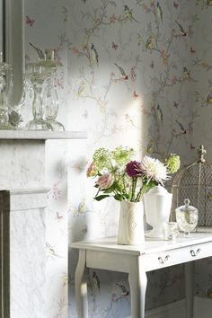 An all over, trailing wallpaper pattern featuring tree branches with vibrant coloured birds, flowers and butterflies.
