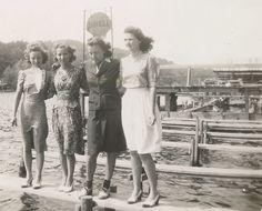 C. 1940s photo of women young women standing on a narrow dock.
