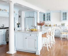 This traditional kitchen gets its fresh, clean look from a pastel blue-and-white color scheme. Custom cabinets with full-inset doors and drawers feature whisper-blue paint accented with hefty black hardware. The sink wall adds white in the form of an informal beaded-board backsplash and a vintage-look apron-front sink. Patterned cushions on white-painted barstools and dining chairs add fresh pops of color.