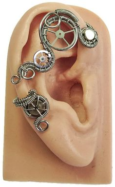 Each handcrafted ear wrap is made with titanium enameled copper wire and features recycled watch parts and stainless steel beads. Ends are