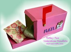 Recycle a flip-top tea box to make a DIY Valentine mailbox craft with paint, a little red plastic or cardboard; brass paper fastener; optional decorations.