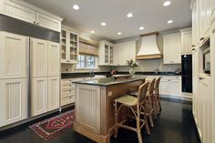 Custom kitchen with white cabinets, blue walls and ceiling, dark floor and wood island all with dark counter tops