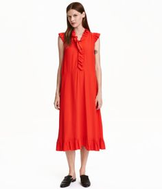 Red. Dress in woven, crêped viscose fabric with ruffles at edges. V-neck at front with buttons. Seam at waist and flared skirt. Unlined.