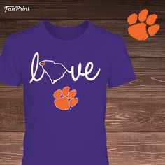 Show your love for Clemson and the state of South Carolina with this officially licensed t-shirt. Available as a t-shirt, tank, hoodie and more! Prices vary according to style.  Check out our full line of awesome Clemson Tigers apparel at https://www.fanprint.com/stores/clemsongearco