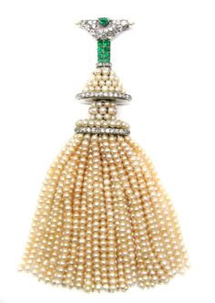 Platinum, pearl, diamond and emerald tassel brooch by Cartier, Paris, the triangular shaped surmount pave-set with old brilliant-cut diamonds, centred by an emerald, with single pearl terminations at the each corner, suspending an emerald and diamond-set panel and pearl-set spacers to the pearl tassels below, mounted in platinum, signed and numbered L5925